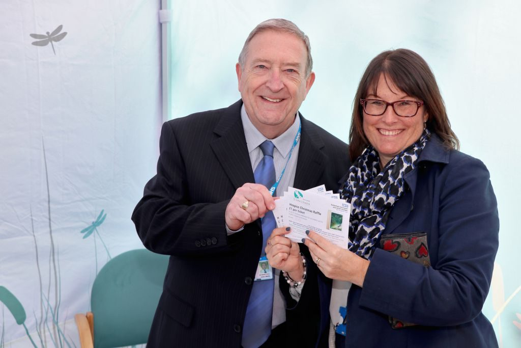 Joanne McDonough, Deputy Chief Operating Officer at RDaSH, is pictured (right) buying tickets from John Wells, of the hospice team.