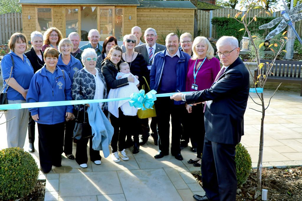 Chairman of RDaSH Lawson Pater is pictured cutting the ribbon surrounded by volunteers, people who have donated to the hospice and staff.