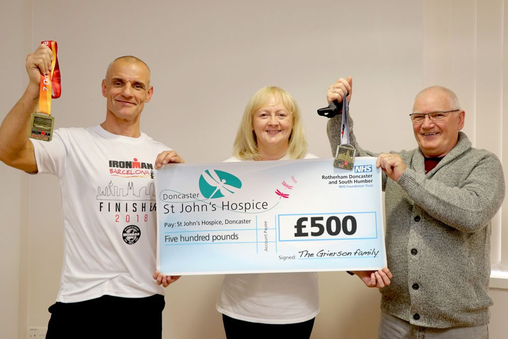 John is pictured (right) together with Lindsey Richards of the hospice and his uncle Sandy Grierson, holding the cheque and his medals.