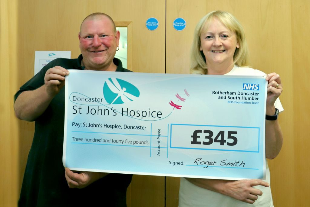 Roger is pictured handing over the cheque to Lindsey of the hospice.