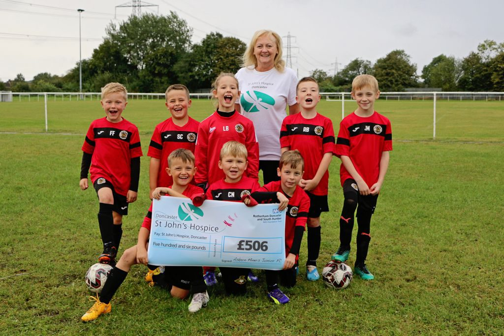 Lindsey Richards of the hospice is pictured with some of the players from Askern Miners Junior Football Club.