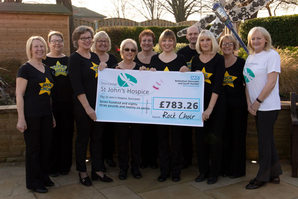 Pictured are members of Rock Choir with Lindsey Richards of the Hospice (far right).
